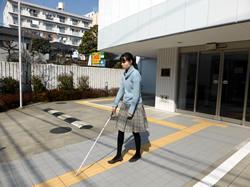 視覚障害者が点字ブロックの上を歩いている写真