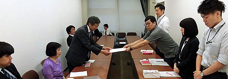 竹下義樹会長が厚生労働省へ要望書を渡している様子