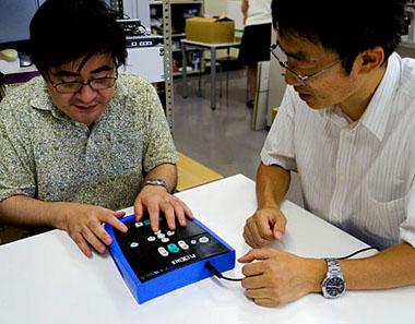 操作方法を説明する白木さんと確認する小川職員